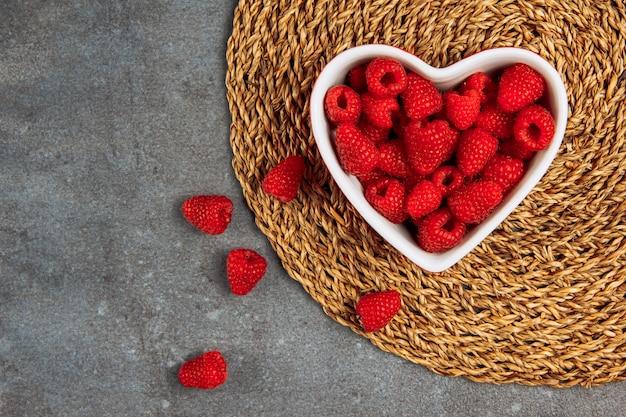 Framboesas de bom gosto em um prato em forma de coração no placemat de vime e fundo cinza asfalto, configuração plana. Foto gratuita