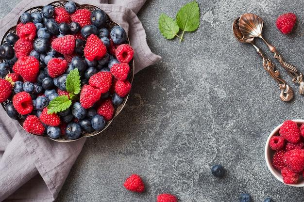 Framboesas frescas e mirtilos em placa na superfície escura Foto Premium
