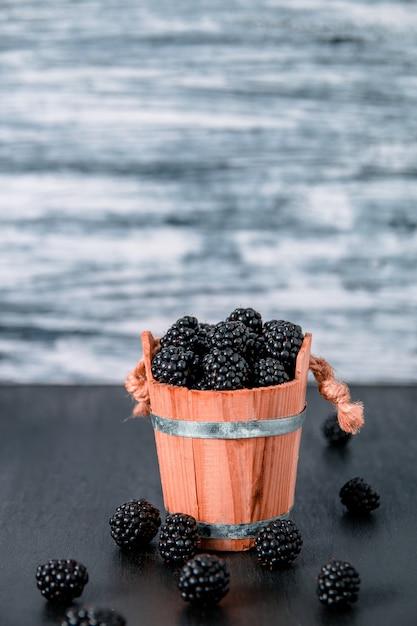 Framboesas pretas uma cesta de madeira e na mesa de madeira preta. copyspace. Foto Premium
