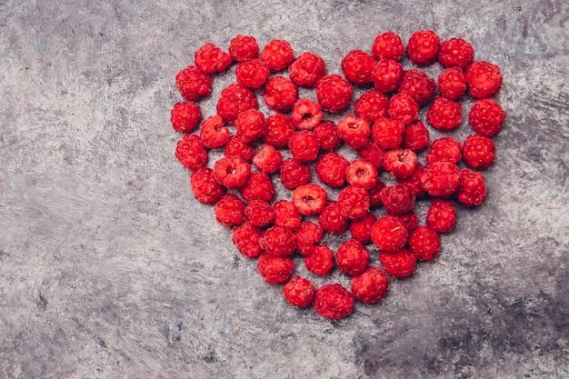 Framboesas vermelhas em forma de coração em uma mesa cinza. vista do topo. Foto gratuita