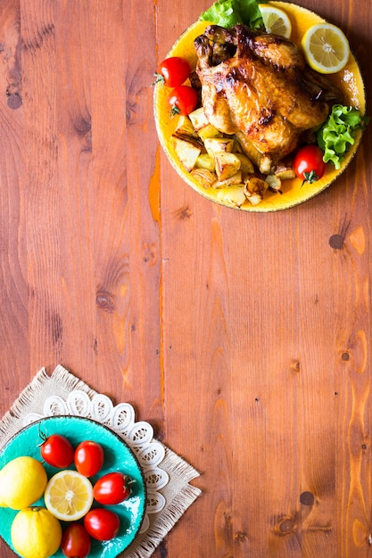 Frango assado caseiro com limão e batatas em um fundo de madeira Foto Premium