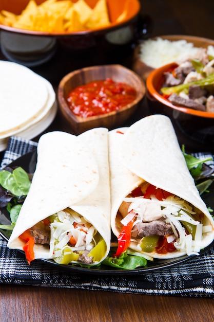 Frango caseiro e fajitas de carne com legumes e tortilhas Foto Premium