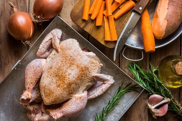 Frango cru temperado, alecrim, legumes picados cenouras batatas cebola alho Foto Premium