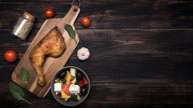 Frango de postura plana na placa de madeira e ingredientes com cópia-espaço Foto gratuita