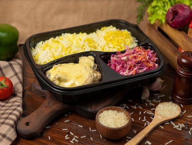 Frango em molho de queijo creme derretido com guarnição de arroz e salada de cenoura repolho para viagem Foto gratuita