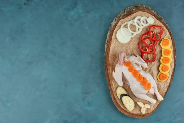 Frango em uma travessa de madeira com legumes. Foto gratuita