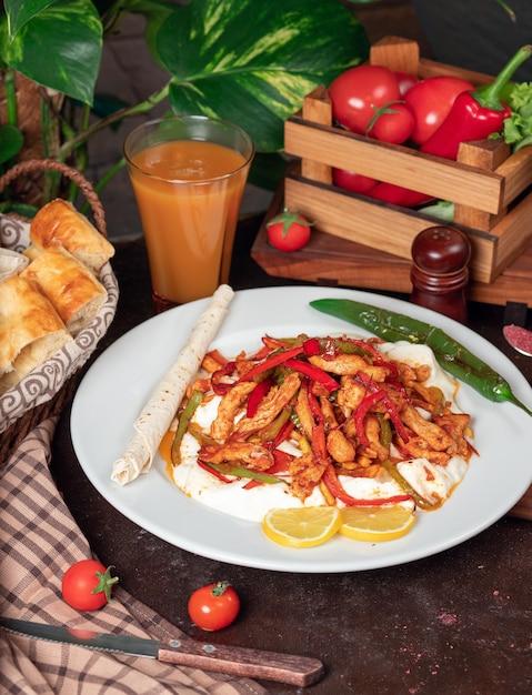 Frango fajita, filé de frango frito com pimentão em panela com fatias de pão em chapa branca Foto gratuita