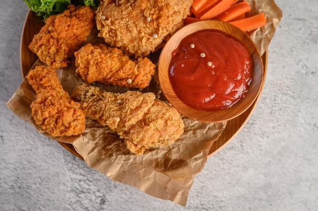 Frango frito crocante em um prato de madeira com molho de tomate e cenoura Foto gratuita
