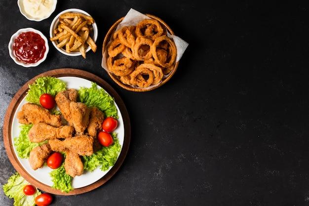 Frango frito e anéis de cebola com espaço de cópia Foto gratuita