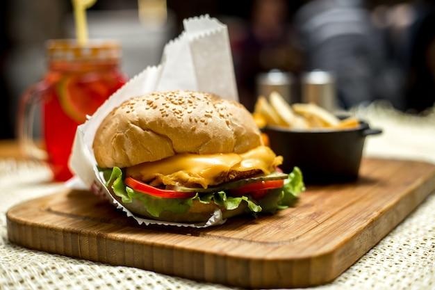 Frango hambúrguer ob placa de madeira alface queijo tomate pepino vista lateral Foto gratuita