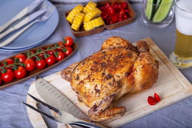 Frango inteiro assado com sal. com espiga de milho, tomate cereja, pepino e pimentão jalapeno. foco seletivo, close-up. Foto Premium