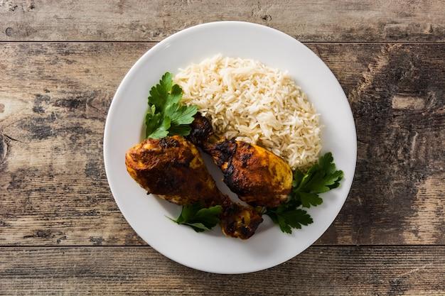 Frango tandoori assado com arroz basmati no prato na mesa de madeira. vista do topo Foto Premium