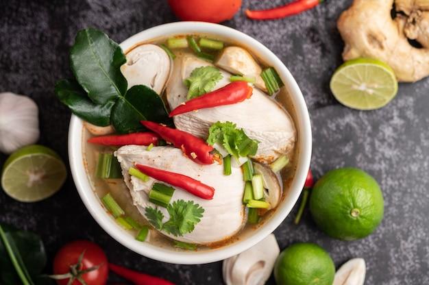 Frango tom yum com pimenta, coentro, pimenta seca, folhas de limão kaffir, cogumelos e capim-limão em uma tigela Foto gratuita