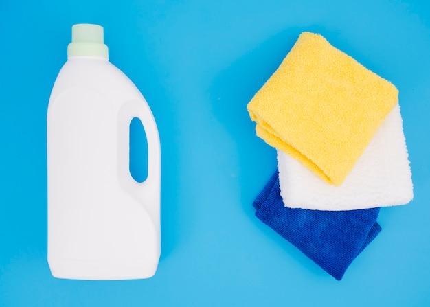 Frasco branco detergente perto do guardanapo multi colorido sobre fundo azul Foto gratuita