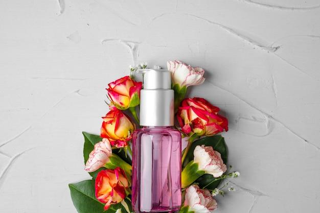 Frasco de fragrância ou óleo aromático em um ramo de flores frescas Foto Premium