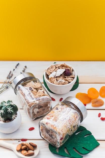 Frasco de granola e flocos de milho perto de frutos secos; folha falsa e planta suculenta na superfície de madeira Foto gratuita