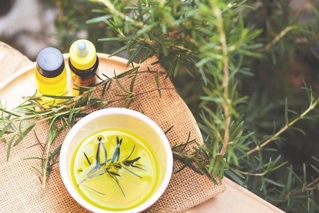 Frasco de óleo essencial ingredientes naturais spa óleo de alecrim para aromaterapia e planta de folhas de alecrim no fundo - cosméticos orgânicos com extratos de ervas Foto Premium