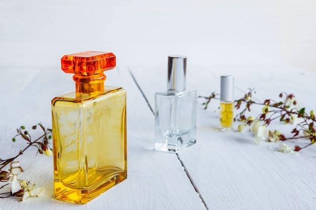 Frasco de perfume com flores sobre fundo branco de madeira Foto Premium