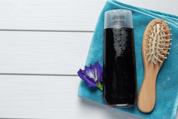 Frasco de shampoo de flor de ervilha borboleta colocado sobre fundo branco de madeira Foto gratuita