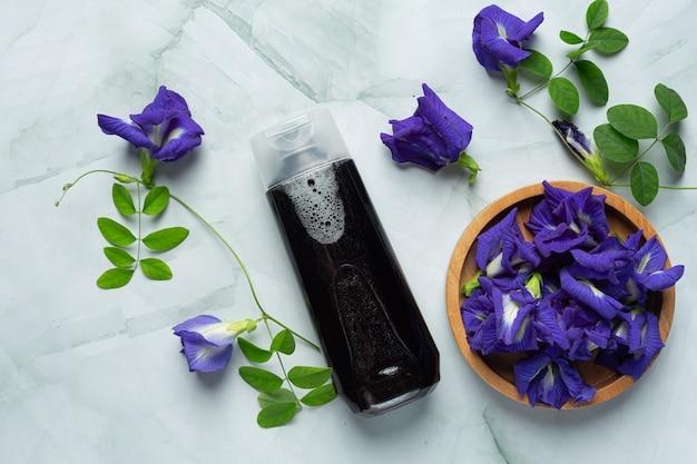 Frasco de shampoo de flor de ervilha borboleta colocado sobre fundo de mármore branco Foto gratuita