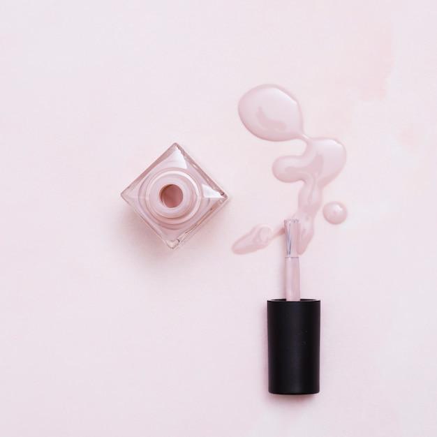 Frasco de verniz de unha derramado com pincel em fundo rosa Foto gratuita