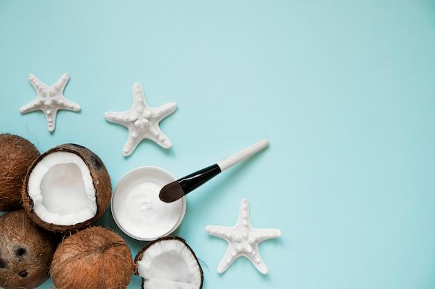 Frasco de vidro aberto com óleo de coco fresco e cocos maduros no azul Foto Premium