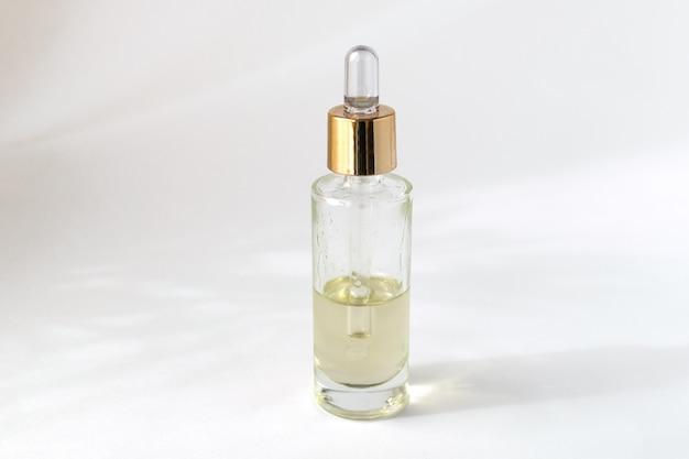 Frasco de vidro conta-gotas com óleo cosmético ou soro, fundo branco Foto Premium