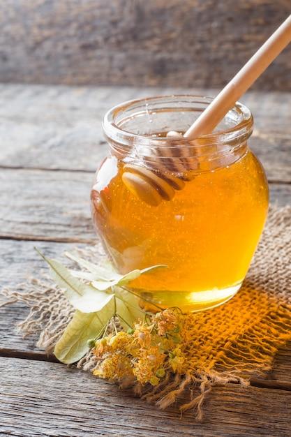 Frasco de vidro de mel, linden flores sobre fundo de madeira Foto Premium
