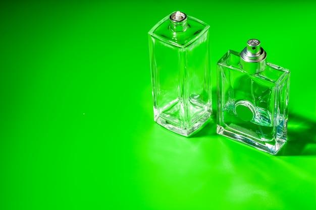 Frasco de vidro de perfume sobre fundo verde claro. Foto Premium