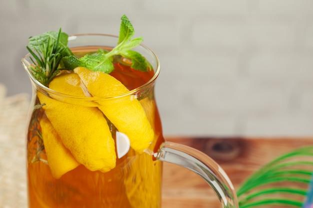 Frasco de vidro do chá verde de gelo com limão, limão, hortelã na mesa de madeira. Foto Premium
