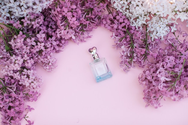 Frasco de vidro e flores lilás no fundo para os termas e a aromaterapia, espaço da cópia para o texto. Foto Premium