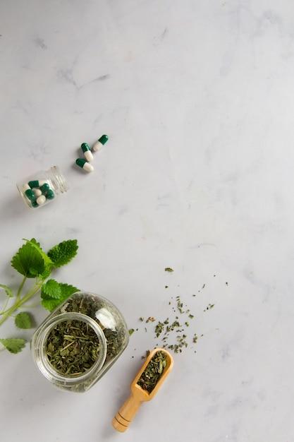Frasco de vista superior com ervas e cápsulas em cima da mesa Foto gratuita