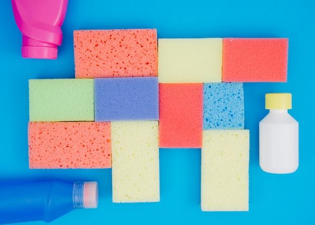 Frasco detergente perto das esponjas multi coloridas sobre fundo azul Foto gratuita