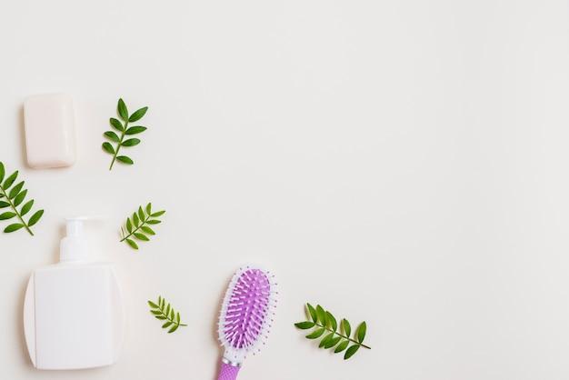 Frasco dispensador; sabão e escova de cabelo com folhas no fundo branco Foto gratuita