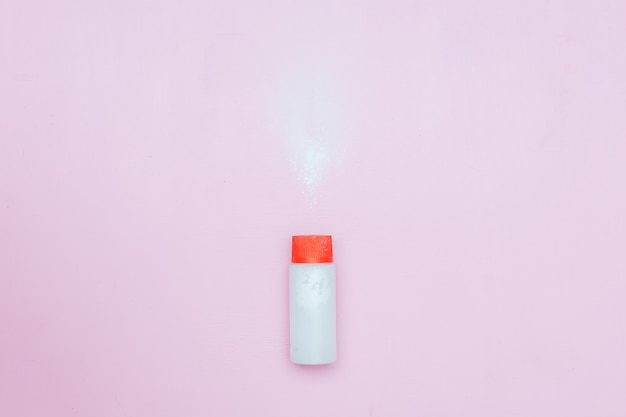 Frasco do pó de bebê do talco no fundo cor-de-rosa. pó derramado do recipiente branco Foto Premium