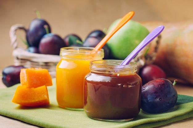 Frascos com comida para bebé e purê de abóbora com colher perto de frutas frescas Foto Premium