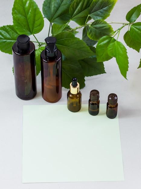 Frascos de cosméticos escuros e folhas naturais verdes sobre um fundo claro Foto Premium