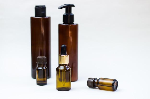 Frascos de cosméticos escuros sobre um fundo claro Foto Premium