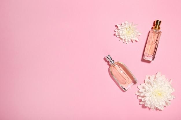 Frascos de perfume com flores em rosa Foto Premium