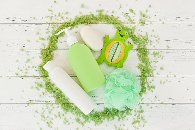 Frascos de shampoo na mesa de madeira. acessórios de banho para bebês. material de banheiro infantil. tubos de banheiro, bálsamo, sal marinho, sabão. Foto Premium