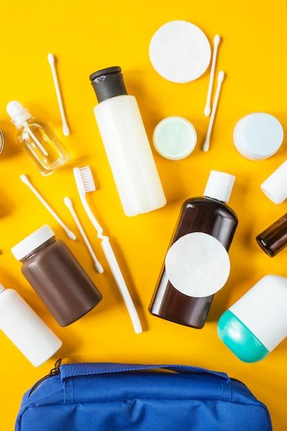 Frascos e recipientes com cosméticos e cotonetes com discos de um saco cosmético azul Foto Premium