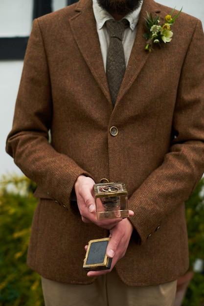 Frase. mãos de um homem em uma jaqueta marrom, segurando uma caixa de presente de vidro com um anel. Foto Premium