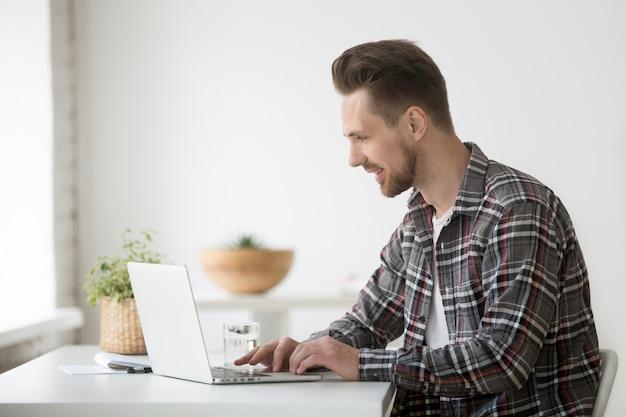 Freelancer de homem sorridente, trabalhando no laptop, comunicando-se online usando o software Foto gratuita