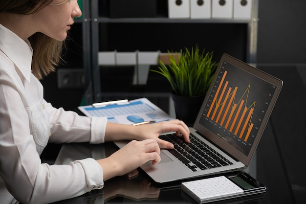 Freelancer digitando no laptop com tela preta em branco próximos gráficos e calculadora Foto Premium
