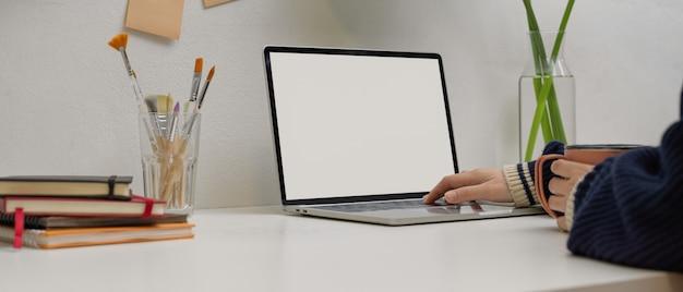 Freelancer feminino digitando no laptop mock-up, mantendo a caneca na mesa branca com suprimentos no escritório em casa Foto Premium