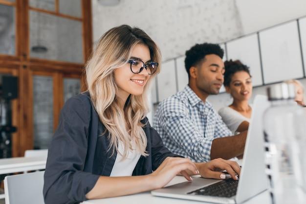 Freelancer feminino encaracolado lindo com manicure bonita usando laptop e sorrindo. retrato interior da secretária loira sentada ao lado de um colega de trabalho africano de camisa azul. Foto gratuita