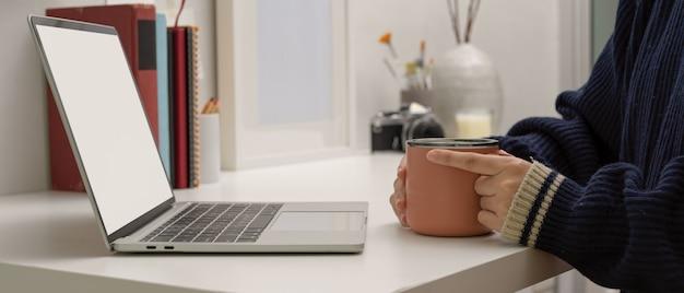 Freelancer feminino sentado em casa, escritório e segurando a caneca de café enquanto procurava no laptop simulado Foto Premium