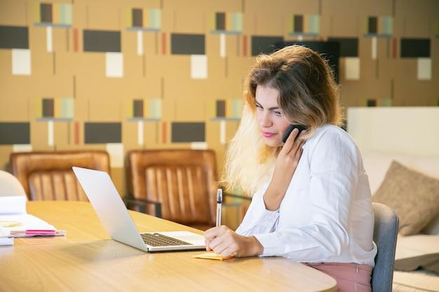 Freelancer focado discutindo projeto com cliente por telefone Foto gratuita