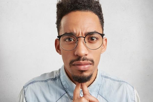 Freelancer masculino confiante usa óculos redondos e parece sério Foto gratuita