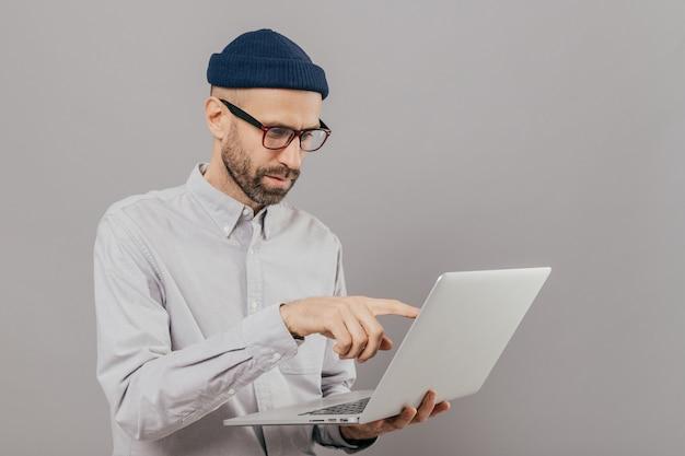 Freelancer masculino faz o trabalho do projeto, pontos com o dedo indicador na tela do computador portátil Foto Premium